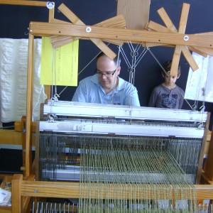 Un treballador de Teixidors treballa amb un teler antic dels que utilitzen diariament al taller de Terrassa (Foto: PV)