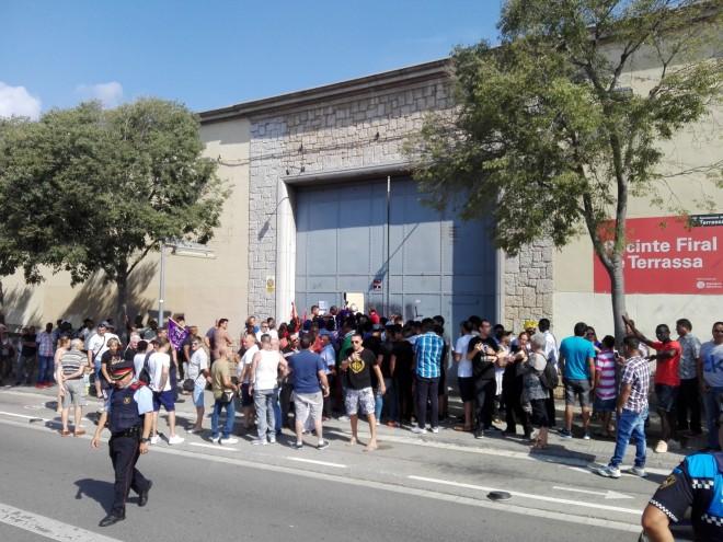 Treballadors i treballadores de la falsa cooperativa TAIC fan cua per entrar a l'assemblea anual, el passat 22 de juliol, a Terrassa. Foto PV